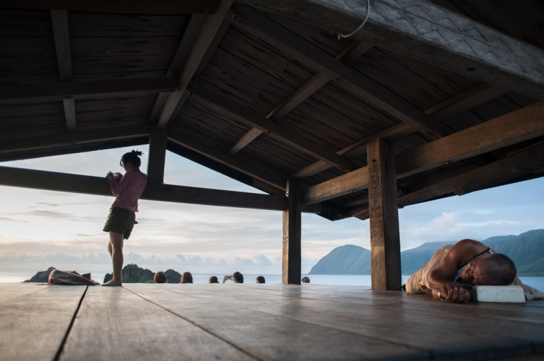 A Taiwanese vacationer takes photos of the sunrise on Orchid Island as a Tao resident sleeps on the beach veranda. Tourism is the only economy on the tiny 17 square mile island.