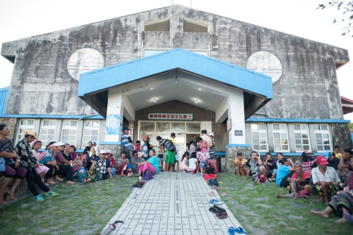 The Tao residents gather and wait outside the community center for the start of of the annual Tao singing competition hosted by TaiPower, the state agency managing the nuclear waste on Orchid Island, Taiwan. All attendants receive a small gifts on behalf of the energy agency for the event.