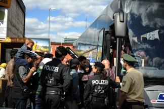 Munich, Germany - Refugees eagerly huddle onto the bus after being processed at Munich Central Station. They are taking to temporary shelters in cities and towns throughout Germany, but are not told where beforhand.
