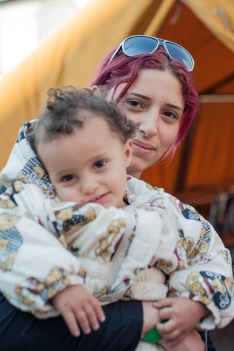 "Oli Al-Thain and her one-year old son, Sanda, from Damascus, Syria arrive in Germany after traveling over one month and crossing six countries. She and her family paid over $200 per person to board a raft with 11 other people to first reach the E.U. through the Greek Islands. They recounted brutality and inhumane treatment in Macedonia where guards ""tossed bread from above like we were animals."""